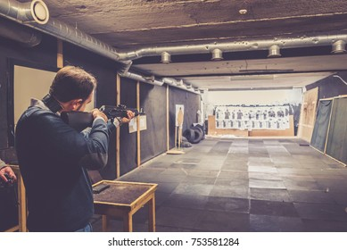Man with weapon try positions for shooting at target in indoor firing range or shooting range
