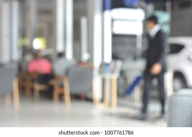 Man wear black suit who is a car salesman and customer who are waiting for a car inspection at the car showroom.Concept for business and services related to vehicles. blurry view.