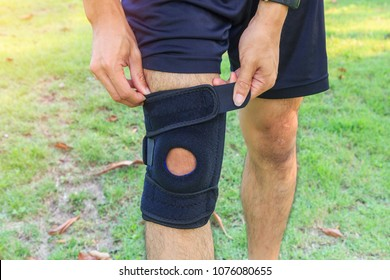 The man wear the Knee Support Brace Patella with sunlight in the park / Knee Pads Hole Sports