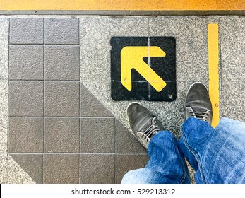 The man wear old shoes and light blue jeans standing in front of yellow arrow left sign of train entrance. Top view.