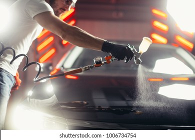 man wear protective mask and eyewear at work. Automobile industry. Car wash and coating business with ceramic coating polishing. Spraying varnish to car.