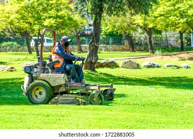Man wear safety mask as a precaution during outbreak the Coronavirus. Essential service. Portrait of single worker in city park mows the grass with lawn mower.