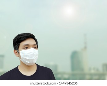 Man wear white face mask because of air pollution in the city.Man worry about contamination open air.Protect body from global warming.Boy wear mask from dust in the town.