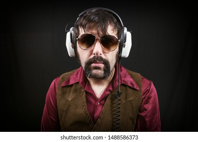 A man wearing 1970's era clothing, including a vest and long collared shirt, and vintage headphones. Recording engineer, radio, disc jockey or just listening to music.