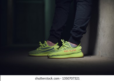 84d6571ad3e97 A man wearing Adidas Yeezy Boost 350 v2 Sply semi frozen yellow sport shoes  shot on