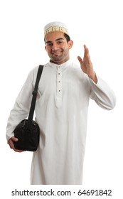 A man wearing a beautiful embroidered robe, thobe, kurta outfit fastened with ruby buttons and wearing a decorative topi hat.  He is waving in a friendly manner.  White background.