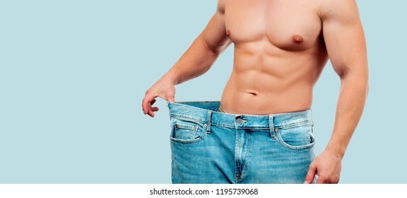Man wearing big jeans after diet, weight loss concept on blue background