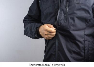 Man wearing black anti static or wet weather jacket or rain coat on white background