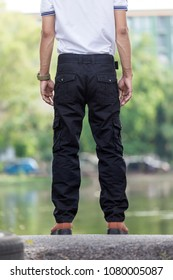 man wearing black cargo pants and standing in the nature park