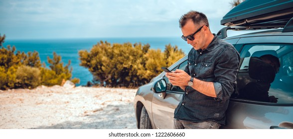 Man wearing black denim shirt and sunglasses lean on car using smart phone by the sea