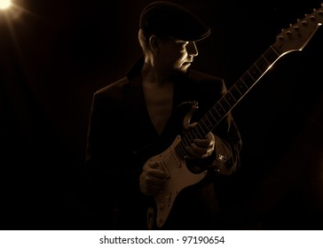 man wearing a black hat , playing guitar on a black background,