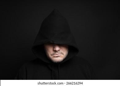 man wearing black hoodie hiding eyes in the dark