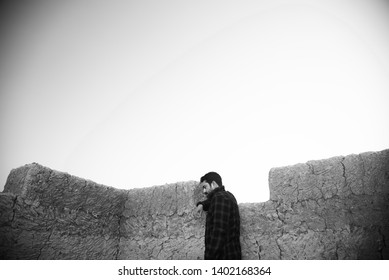 Man wearing black shirt standing around a clay made structure