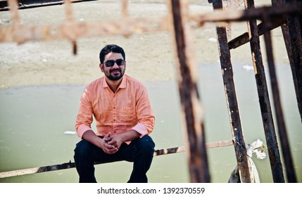 Man wearing black sunglass and jeans sitting in a place