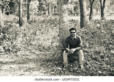 Man wearing black sunglass sitting around a forest area