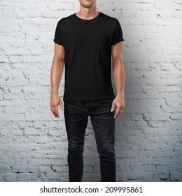 Man wearing black t-shirt. Brick wall background