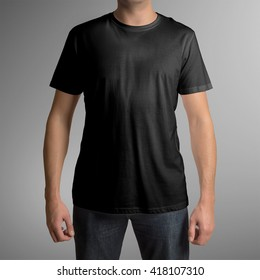 Man wearing black t-shirt isolated on gray background, with clipping path to change background