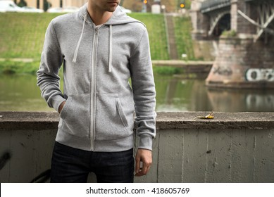 Man wearing blank grey hoodie, in the urban background near the river