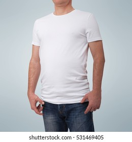 Man wearing blank t-shirt isolated on gray background with copy space. Tshirt design and people concept - close up of man in blank white t-shirt isolated. For mock up template design. View front