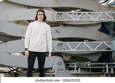 Man wearing blank white sweatshirt standing over gray background. Sweatshirt or hoodie for mock up, logo designs or design print with with free space.