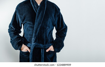 A man wearing a blue bathrobe, bathrobes is holding his hands in his pocket. The concept of rest, a day off work. The sick man spends his day off at home, resting in front of the TV.