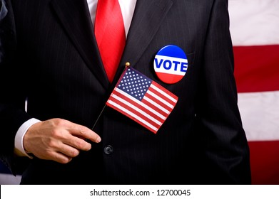 A man wearing a blue business suit and tie with a vote button and US flag.  Election day background or concept