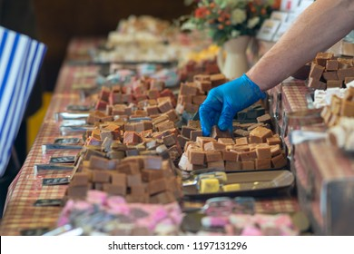 man wearing blue glove handles sample of fudge on a market stall