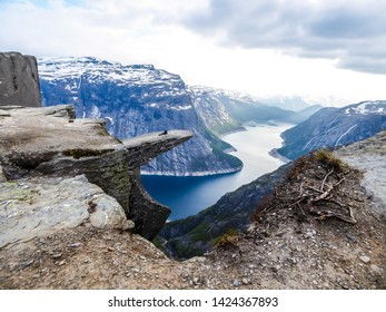 A man wearing blue jacket sits at the hanging rock formation, Trolltunga with a view on Ringedalsvatnet lake, Norway. Slopes of the mountains are partially covered with snow. Freedom and happiness