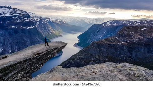 A man wearing blue jacket stands at the hanging rock formation, Trolltunga with a view on Ringedalsvatnet lake, Norway. Slopes of the mountains are partially covered with snow. Freedom and happiness