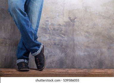 Man wearing blue jeans, long legs, wearing black leather shoes, standing on a wooden floor, behind a mortar. Style, fashion and design
