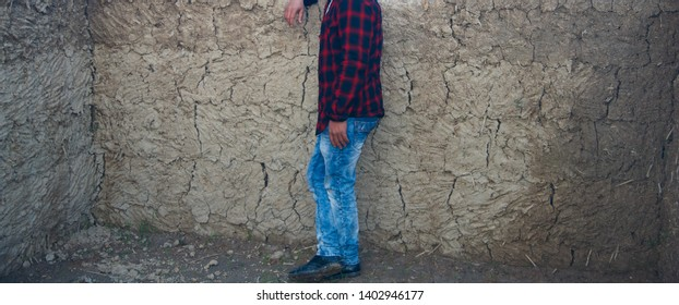 Man wearing blue jeans and shirt standing in a place
