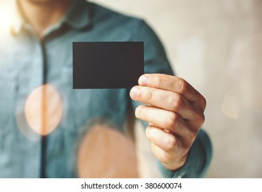 Man wearing blue jeans shirt and showing blank black business card. Blurred background. Horizontal mockup