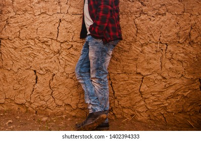 Man wearing blue jeans standing in a place with brown background photo