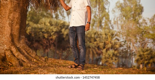 Man wearing blue jeans standing beside an old tree