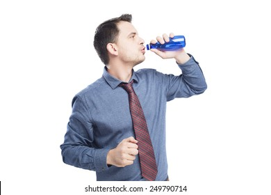 Man wearing a blue shirt and red tie. He is drinking from blue bottle. Over white background