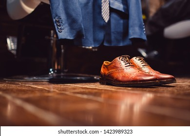 Man wearing a blue suit putting his brown shoes on. Hands and shoe close-up. Closeup view of male hands lacing beautiful elegant shoes.