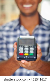 Man wearing blue white square pattern shirt holding up credit card payment terminal in front of camera