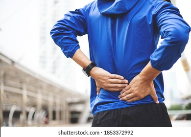 A man wearing a blue Windbreaker jacket., Back injury after exercise concept.It happens often in athletes practice overtain,Lifting heavy objects .In a Muscle inflammation concept.