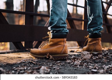 man wearing boots standing on bridge