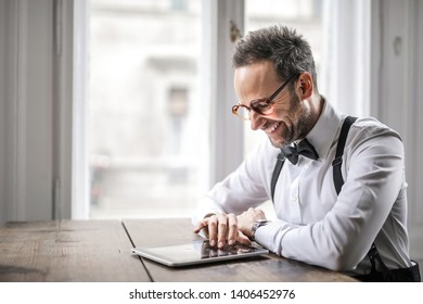 Man wearing bow tie checking happily his tablet.