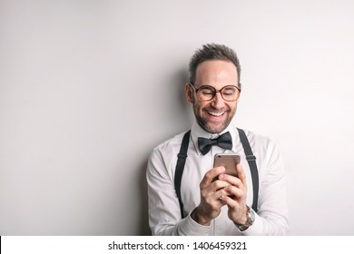 Man wearing bow tie checking happily his smartphone.