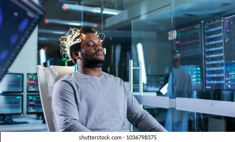 Man Wearing Brainwave Scanning Headset Sits in a Chair With Closed Eyes. In the Modern Brain Study Laboratory Monitors Show EEG Reading and Brain Model.