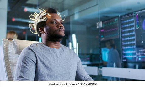 Man Wearing Brainwave Scanning Headset Sits in a Chair in the Modern Brain Study Laboratory Monitors Show EEG Reading and Brain Model.