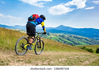 A man wearing bright clothing, riding enduro bicycle.Picture with background of blue mountain range. Sunny summer day