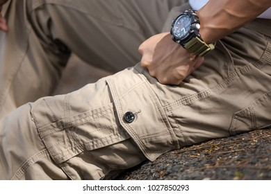 Man wearing brown cargo pants and sitting in the nature park