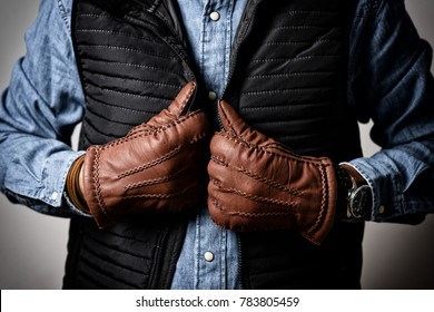 A man wearing the brown leather gloves in winter.