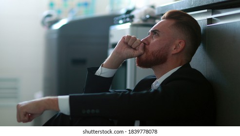 Man wearing business suit sitting on home floor feeling despair and anxiety for the future