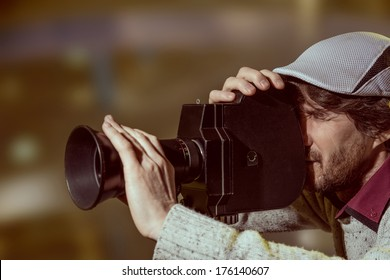 A man wearing a cap with an old movie camera. Shooting reportage
