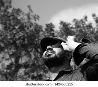 Man wearing cap and sunglass standing in a place unique photo