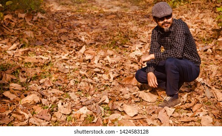 Man wearing cap and sunglasses sitting in a place unique photo